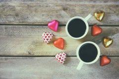 Imagem da vista superior de chocolates coloridos da forma do coração, coração da tela e canecas dos pares de café na tabela de ma Imagem de Stock