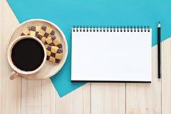 A imagem da vista superior do caderno aberto com página vazia e copo de café no fundo de madeira, apronta-se adicionando ou zomba Fotografia de Stock Royalty Free