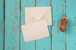 Imagem da vista superior do papel e do envelope vazios de letra ao lado dos lápis coloridos na tabela de madeira vintage filtrado Fotografia de Stock