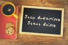 Imagem da vista superior do quadro-negro com a parada da frase que sonha o começo que faz, ao lado do copo de café e das cookies Imagens de Stock Royalty Free