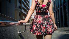Imagem da vista traseira da mulher 'sexy' na mão curto da terra arrendada do vestido no corrimão do metal ao andar na rua fotografia de stock royalty free