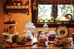 Imagem das especiarias e da erva arranjadas ordenadamente no vidro e na escala na cozinha foto de stock