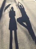 Imagem das mulheres que mantêm um guarda-chuva e um homem que fazem a pose da árvore fotos de stock royalty free