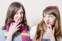 Imagem das namoradas de sorriso felizes bonitas das jovens mulheres que têm o divertimento que veste o lenço feito malha Fotografia de Stock Royalty Free