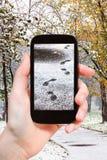 Imagem das pegadas na primeira neve no parque da cidade Imagens de Stock