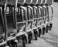 imagem das rodas da fileira dos carrinhos de compras estacionados equipados com os mecanismos de travamento a fichas Fotografia de Stock