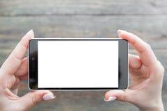 Imagem de agarramento no smartphone, fundo de madeira imagem de stock