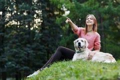 Imagem de baixo da mulher que aponta para a frente ao lado do cão no gramado verde foto de stock royalty free