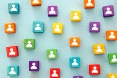 imagem de blocos coloridos com ícones dos povos sobre a tabela de madeira, recursos humanos e conceito da gestão Foto de Stock