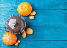 Imagem de cima da bandeja do ferro com tampa, vegetais, batatas, abóboras, cebolas Fotos de Stock