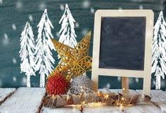 Imagem de decorações e de quadro do Natal ao lado do fundo do quadro-negro com os desenhos do conceito do inverno Foto de Stock