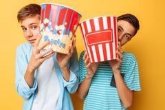 Imagem de dois adolescentes amedrontados, indivíduos que olham um filme de terror e que escondem atrás de uma cubeta da pipoca em imagens de stock