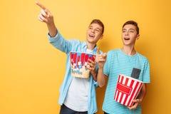 A imagem de dois excitou adolescentes bonitos, indivíduos que olham um filme interessante e que comem a pipoca em um fundo amarel foto de stock royalty free