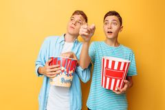 A imagem de dois excitou adolescentes bonitos, indivíduos que olham um filme interessante e que comem a pipoca em um fundo amarel fotografia de stock royalty free