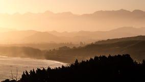 Imagem de fundo calma de raios e de névoa do sol através das montanhas fotos de stock royalty free