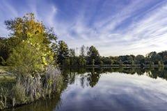 Imagem de fundo de um lago com folliage da queda e do céu azul com Imagem de Stock Royalty Free