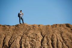 Imagem de longe do homem do turista com as varas para andar no monte contra o céu azul Foto de Stock Royalty Free