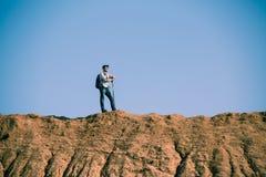Imagem de longe do homem do turista com as varas para andar no monte contra o céu azul Imagem de Stock