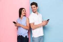 Imagem de pares otimistas usando telefones celulares junto, isolado imagem de stock royalty free