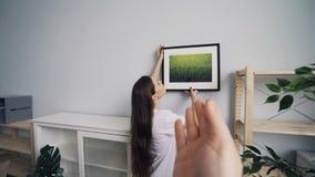 Imagem de suspensão da menina bonita na parede quando homem que escolhe o lugar que mostra os polegares-acima