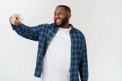 Imagem de tomada feliz de sorriso do autorretrato do selfie do homem negro afro-americano novo com telefone celular fotos de stock royalty free