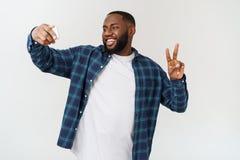 Imagem de tomada feliz de sorriso do autorretrato do selfie do homem negro afro-americano novo com telefone celular imagem de stock