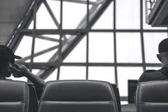 A imagem de trás preto e branco de um homem que senta-se e que espera partir quando um outro homem que fala em um telefone imagens de stock royalty free