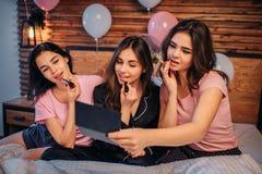 Imagem de três adolescentes que fazem a composição Puseram algum batom sobre os bordos e olhar no espelho As meninas são concentr imagens de stock