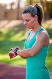 Imagem de um atleta fêmea que ajusta seu monitor da frequência cardíaca Foto de Stock