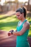 Imagem de um atleta fêmea que ajusta seu monitor da frequência cardíaca imagem de stock royalty free