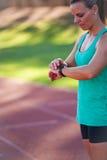 Imagem de um atleta fêmea que ajusta seu monitor da frequência cardíaca imagens de stock