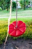 Imagem de um balanço vermelho, redondo para crianças no quintal imagem de stock royalty free