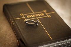 Imagem de um close-up da Bíblia do livro no emperramento de couro preto com um zíper com um peixe cristão do símbolo do pendente  Imagens de Stock