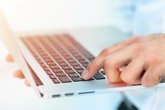 Imagem de um dedo que está a ponto pressionar a chave no teclado do portátil Fotos de Stock