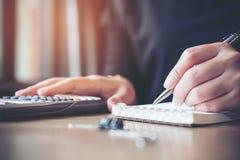 Imagem de um funcionamento da mulher de negócio, escrita no caderno e calculadora do close up da utilização Imagens de Stock