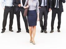 Imagem de um grupo de homens de negócios novos que estão com uma mulher de negócios que anda na parte dianteira Fotografia de Stock