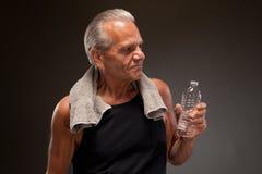Imagem de um homem superior que levanta com garrafa de água e toalha Imagem de Stock
