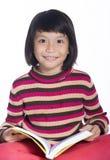 Imagem de um sorriso da menina que guarda um livro no fundo branco Foto de Stock