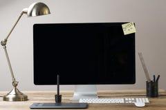 Imagem de um tela de computador grande com uma lâmpada e uns artigos estacionários Fotografia de Stock Royalty Free