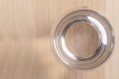 Imagem de um vidro meio cheio da água que está em uma tabela de madeira imagens de stock royalty free