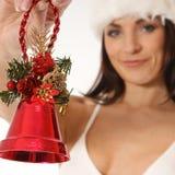 Imagem de uma menina em um chapéu do Natal que prende um sino Foto de Stock Royalty Free