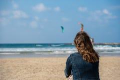 Imagem de uma mulher na praia que olha dois kitesurfers no mar fotos de stock