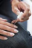 Imagem de uma mulher que aplica o verniz para as unhas em seu prego com cuidado Foto de Stock Royalty Free