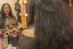 Imagem de uma mulher que olha si mesma no espelho após uma composição profissional fotografia de stock royalty free
