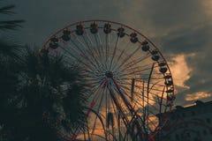 Imagem de uma roda de ferris em um dia nebuloso durante o por do sol fotografia de stock royalty free