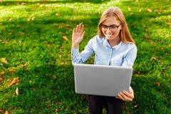 A imagem de uma senhora surpreendente nova, sentando-se em um parque, usando um laptop, senta-se em um gramado verde fotografia de stock royalty free