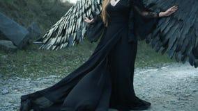 Imagem desagrad?vel, menina infeliz com as asas pretas grandes e chifres pesados apenas na cabe?a no vestido escuro de voo longo  filme