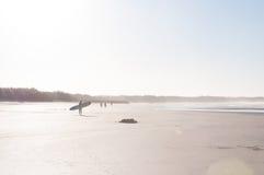 Imagem distante da praia de Person With Surfboard Walking At imagem de stock royalty free