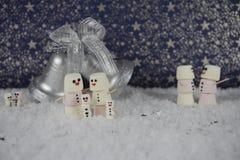 Imagem do ano novo do Natal de alguns marshmallows dados forma como o boneco de neve na neve com teste padrão de estrelas no fund Imagem de Stock Royalty Free