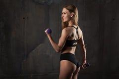 A imagem do atleta fêmea novo muscular que veste o desgaste preto do esporte está com à sua de volta à câmera no fundo escuro foto de stock royalty free